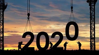 Sihouette of builders placing the numbers 2020 on the ground