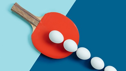White eggs on table with a ping pong bat