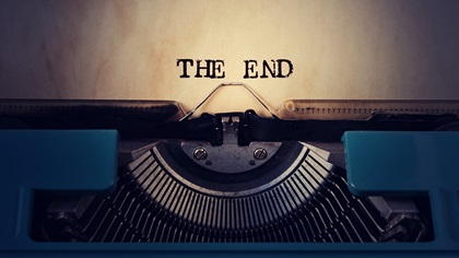Close up of old blue typewriter with text stating the end on paper
