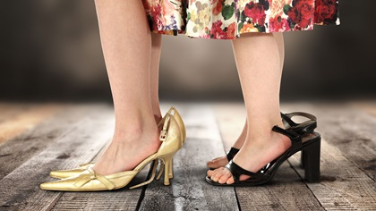 Two pairs of feet standing in highheels