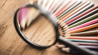 Bunch of colourful pencils under a magnifying glass