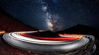 Cars leaving light trails at night with beautiful sky above