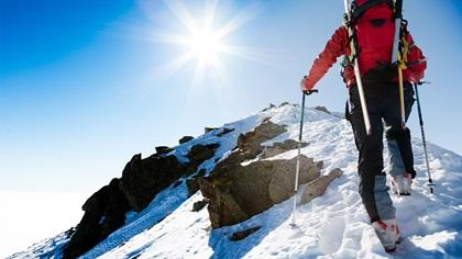 Mountaineer walking along snowy ridge with skis