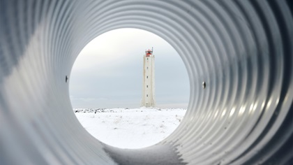A lighthouse behind a pipe in winter