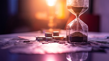 Sand timer running out of time next to coins