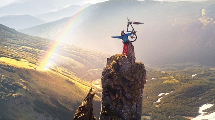 Person on top of a high mountain rock and holding their bike up, with a lovely rainbow in the background