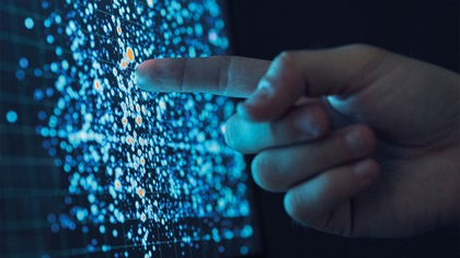 Person pointing at screen showing computer technology such as binary code