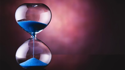 A glass timer with blue sand