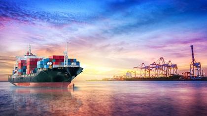 Trade ship at sunset near dock
