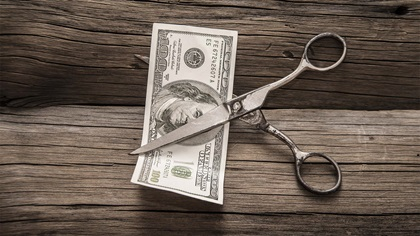 Scissors about to cut in half a one-hundred dollar note