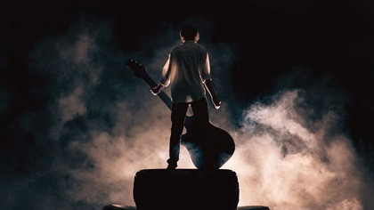 Musician plays guitar on stage