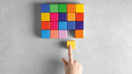 Person moving colour block into a bunch of other colour blocks