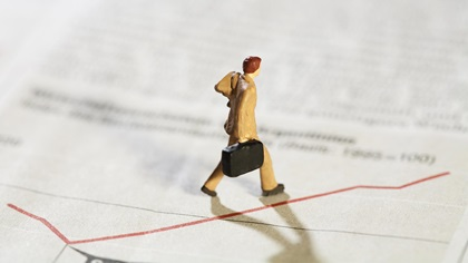 Toy figure of man walking along a graph which is increasing
