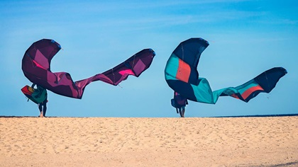Two friends on a beach with big butterfly wing kites