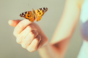 Girl with a butterfly resting on her finger