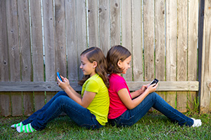 two girls sitting back to back on mobile phones