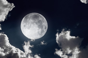 Full moon high in clouds