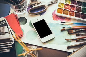 Smartphone on an artist's desk with watercolour paints and brushes.