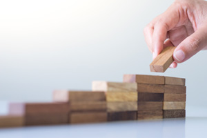 Person adding more and more wooden blocks to pile showing an increase