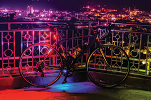 Colour night with bicycle against a fence