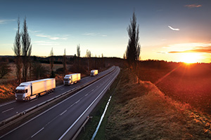 Trucks on the road during sunset