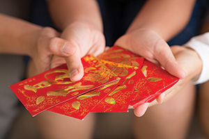 Close up of Vietnamese red envelopes with money being presented