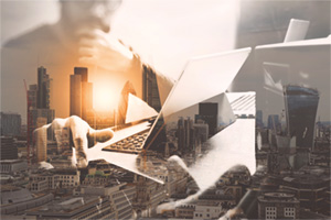 Business man on laptop overlayed with a cityscape