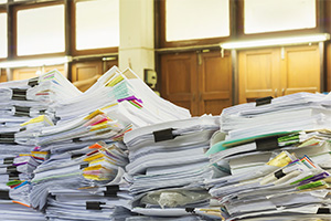 Towers of paper documents on a desk, unsorted