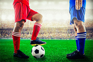 Two footballers, one in red kit and the other in blue kit, standing face to face with each other