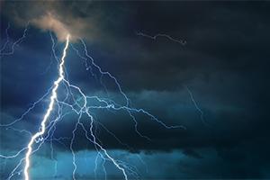 Fork lightning striking down from a dark cloudy sky