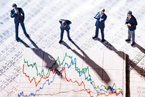 Model figurines of businessmen looking skeptical at stock market chart